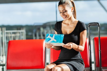 Young businesswoman looking at air ticket