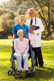 Healthcare workers outdoors with disabled senior patient