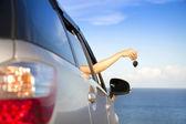 Ruka ženy držící klíč od auta