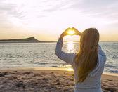 Dívka drží za ruce ve tvaru srdce na pláži