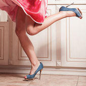 Gyönyörű nő lába kék high heel cipő, piros ruhás