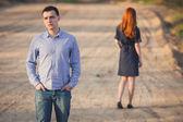 Smutný muž a žena stojí na polní cestě