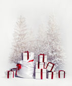 Christmas trees with heap of gift boxes over white background