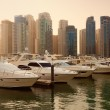 Постер, плакат: Skyscrapers and Yachts in Dubai Marina During Sunset