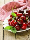Třešně jahody s mátou listy na dřevěný stůl