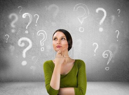 Beautiful woman with questioning expression and question marks a