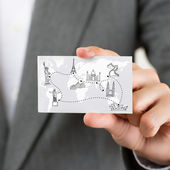 Businesswoman holding business card with world map and famous to
