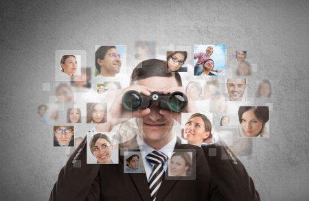 Business man looking for employees through binoculars.