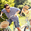 Постер, плакат: Happy couple riding bikes