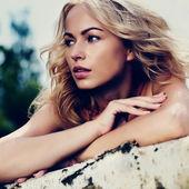Frau mit blonden Haaren auf Zweig. schaut sich um