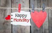 Felice Lunedi su carta istantanea e piccoli cuori rossi appesi sul bucato. sullo sfondo di legno vecchio