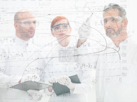 Постер, плакат: Scientists discussing a diagram, холст на подрамнике