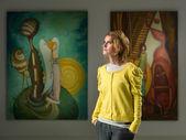 Vista ritagliata di donna caucasica in piedi e in posa in una galleria darte, guardando lontano