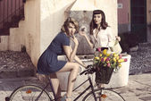 Couple of fashion girls with bicycle