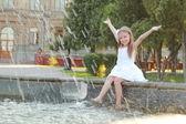 Veselé roztomilé děvčátko v bílých šatech sedí u fontány a usmívá se na letní téma
