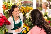 Happy florist writing flower shop talking customer
