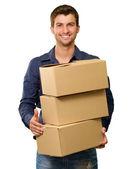 Mladý muž, který držel stack lepenkových krabic