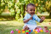 Ritratto di un ragazzo piccolo bambino afro-americano giocando allaperto in erba