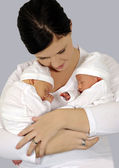 Junge Mutter mit zwei Babys in weiße Kleidung