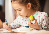 Malá holčička malování vajec na křesťanské Velikonoce