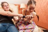 Malá holčička tahání tv vzdálené z dospělých sestra