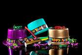 Colorati cappelli Capodanno compreso il verde, viola, rosa, oro e rosso, stelle filanti, i responsabili del rumore e coriandoli su sfondo nero