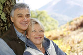 Portrait of smiling senior couple leaning against tree