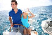 Junges Paar auf einer Yacht im karibischen Meer navigieren
