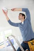 Electrician installing fire alarm inside house
