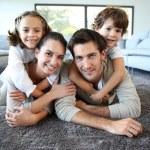 Smiling family on carpet