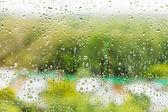 Dešťové kapky na okenní sklo v letní den