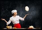 Asian female chef tosses a piece of dough