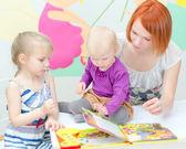 Madre e le sue figlie leggendo un libro