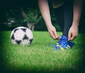 Fotbalista zavázat boty na hřištiフィールドで彼の靴を結ぶことのフットボール選手