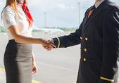 Pilot und Stewardess Händeschütteln auf Flugplatz-Hintergrund