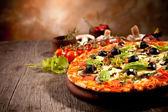 Deliziosa pizza fresca servita sul tavolo di legno