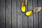 Due stivali gialli con fiori gialli accanto