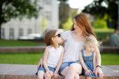 Giovane madre e le sue figlie allaperto in estate