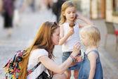 Giovane madre e le sue figlie mangiare gelato allaperto
