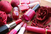 A collection of makeup: lipsticks, lip gloss and nail polishes decorated with red potpourri all in red and pink shades