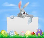 The Easter bunny pointing at a sign with Easter eggs background