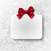 White paper abel with red silk ribbon on gray paper with snowflake pattern Christmas background