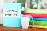 Kiste Waschmittel mit blauen Mess-Cup und Handtücher, mit Holztisch Nahaufnahme