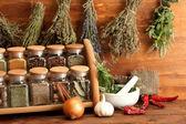 Sušené byliny, koření a a pepřem, na dřevěné pozadí