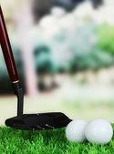 Golfové míčky a řidič na zelené trávě venkovní zblízka