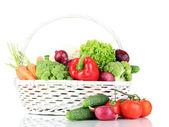 čerstvá zelenina v bílém proutěném koši na šedém pozadí