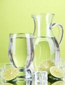 Sklenice džbán vody a skla na zeleném pozadí