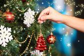 Zdobení vánočního stromu na světlé pozadí