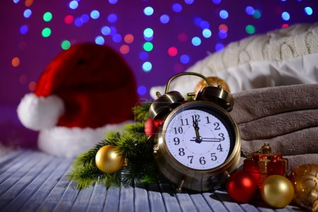 Composition with retro alarm clock and Christmas decoration on bright background