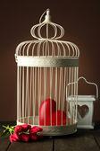 Srdce v dekorativní klec na dřevěný stůl, na hnědé pozadí